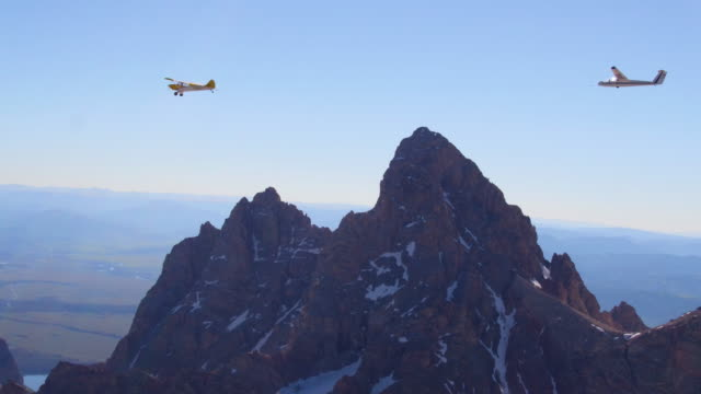 Aerial view of a Glider releasing from a tow airplane in front of the Grand Teton.