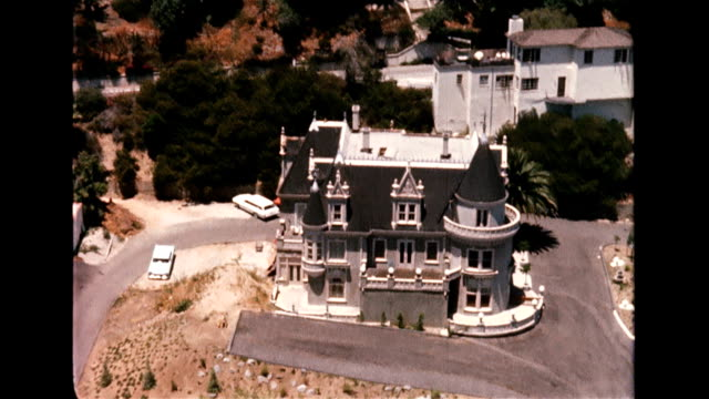 stockvideo's en b-roll-footage met / aerial view of a grey mansion with turrets. magic castle mansion on january 01, 1956 in hollywood, california - hollywood californië