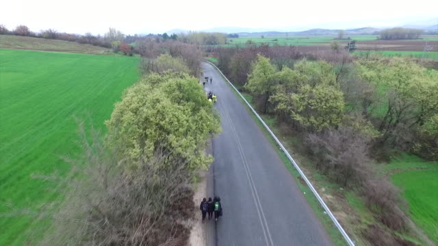 aerial view of a group of migrants walking a country road towards idomeni camp in greece - macedonia country stock videos and b-roll footage