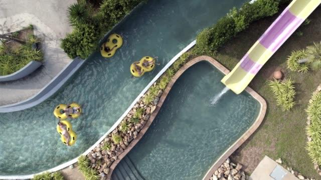 luftaufnahme von einer gruppe von menschen genießen in einem wasserpark auf aufblasbaren ringen - wasserrutsche stock-videos und b-roll-filmmaterial