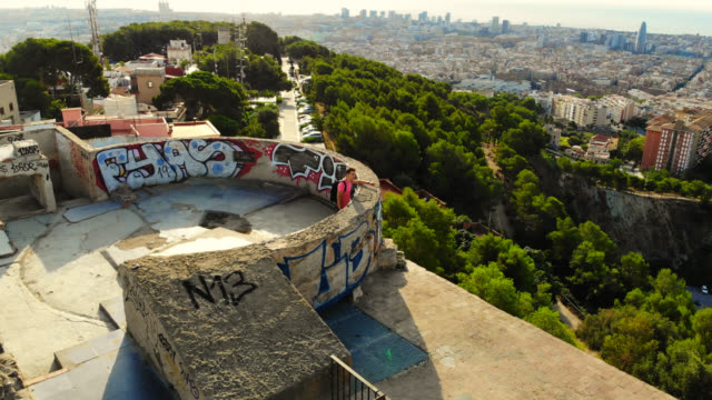 stockvideo's en b-roll-footage met aerial view of a guy in the military bunkers viewpoint over barcelona city during sunrise. - draaien lichaamsbeweging