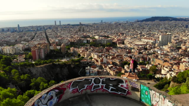 vidéos et rushes de aerial view of a guy walking at the edge of the military bunkers viewpoint over barcelona city during sunrise. - barcelone espagne