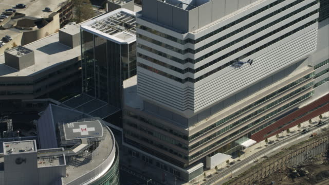 vídeos de stock, filmes e b-roll de aerial view of a helicopter approaching and landing at children's hospital of philadelphia. shot in 2011. - helicopter landing pads
