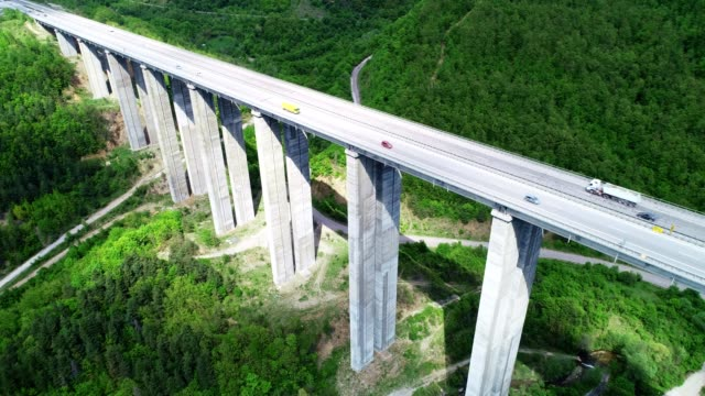 aerial view of a highway on a viaduct high tech engeneering construction, springtime green colored landscape and clear blue sky - viaduct stock videos & royalty-free footage
