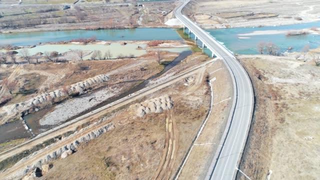 luftaufnahme einer autobahn auf einem viadukt, high-tech-engeneering-konstruktion, ockerfarbene landschaft und dramatischer himmel, zeitraffer - bulgarien stock-videos und b-roll-filmmaterial