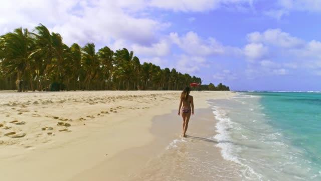 ココナッツの木、砂、波とターコイズブルーの海で熱帯の島のビーチでリラックスして歩くヒスパニック系の若い女性の空中写真 - idyllic点の映像素材/bロール