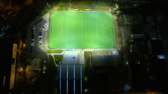 vídeos de stock, filmes e b-roll de aerial view of a hockey sports ground at night. - david ewing