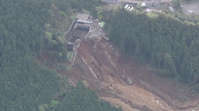 aerial view of a huge landslide caused by consecutive earthquake attacks during 2016 kumamoto earthquakes: panning to houses buried in landslide in... - 地震点の映像素材/bロール