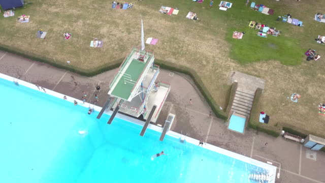 aerial view of a huge public swimming pool above the diving tower in göttingen in germany while a lot of people are enjoying the beautiful weather... - diving platform stock videos and b-roll footage
