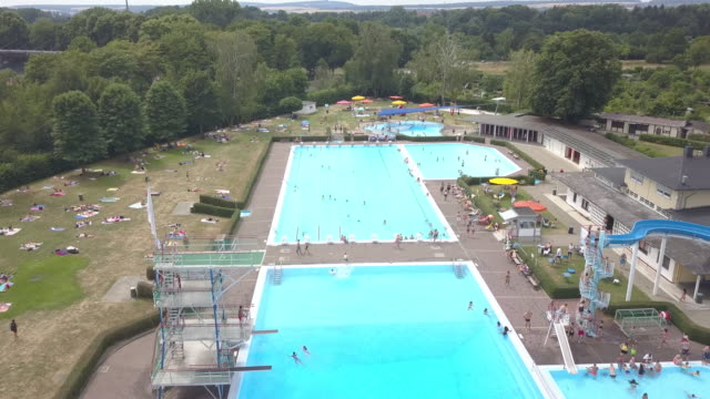 Aerial view of a huge public swimming pool in Göttingen in Germany while a lot of people are enjoying the beautiful weather are swimming jumping from...