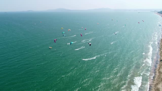 aerial view of a kite surf regatta on the sea coastline, turquoise water, competition, water sports, event, racing, extreme sports, adventure, travel destinations, wanderlust - kiteboarding stock videos & royalty-free footage
