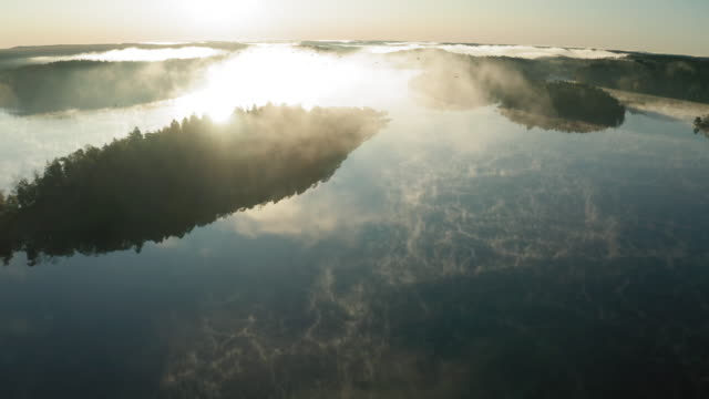 aerial view of a lake covered by beautiful mist on an autumn morning - approaching stock videos & royalty-free footage