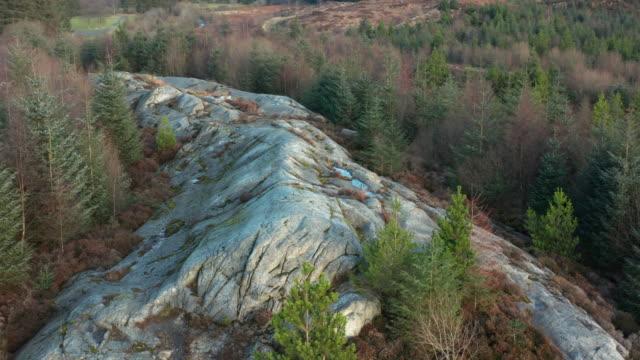 luftaufnahme eines großen granitvorsprungs in einem gebiet des schottischen waldes in dumfries und galloway - granit stock-videos und b-roll-filmmaterial