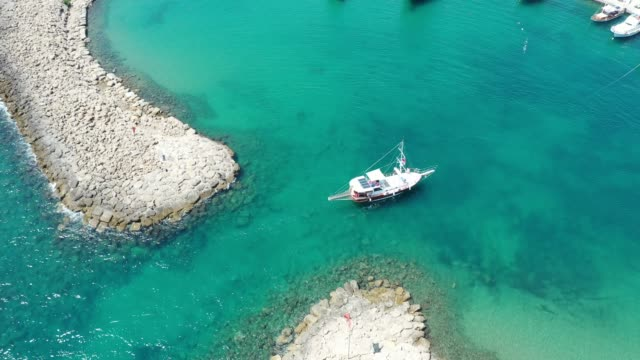 aerial view of a little yacht on the entrance of marina - marina stock videos & royalty-free footage