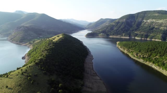 aerial view of a majestic winding riverbed with green hills and vast nature skyline around, panoramic point of view. - sustainable tourism stock videos & royalty-free footage