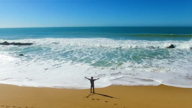 vidéos et rushes de aerial view of a man alone in an amazing and unspoiled beach in the spain coast - rivage