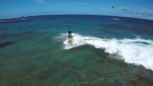 aerial view of a man crashing while doing a kitesurfing trick  in hawaii. - kite sailing stock videos and b-roll footage