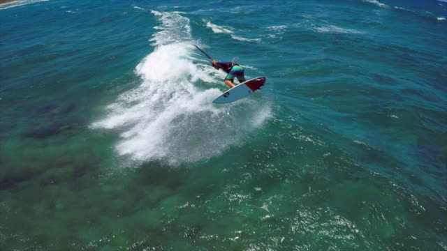 aerial view of a man kitesurfing in hawaii. - slow motion - wassersport stock-videos und b-roll-filmmaterial