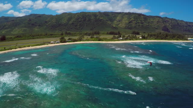 aerial view of a man kitesurfing in hawaii. - kite sailing stock videos and b-roll footage