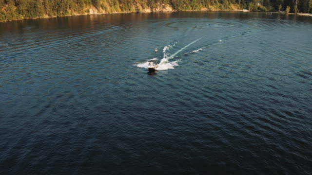 aerial view of a man riding a hydrofoil behind a ski boat - barca a motore video stock e b–roll