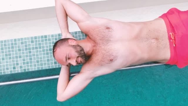 vidéos et rushes de vue aérienne d'un homme, un bain de soleil de la piscine à débordement - infini