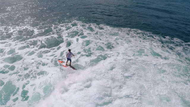 aerial view of a man sup stand-up paddleboard surfing in hawaii. - zoom out stock videos & royalty-free footage