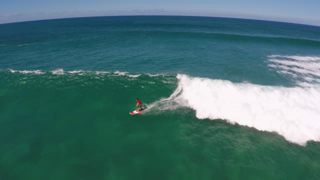 aerial view of a man sup stand-up paddleboard surfing in hawaii. - wipeout stock videos & royalty-free footage