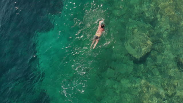 aerial view of a man swimming in aegean sea - bay of water stock videos & royalty-free footage