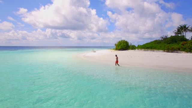 aerial view of a man walking on the beach around a tiny deserted tropical island. - orizzonte sull'acqua video stock e b–roll