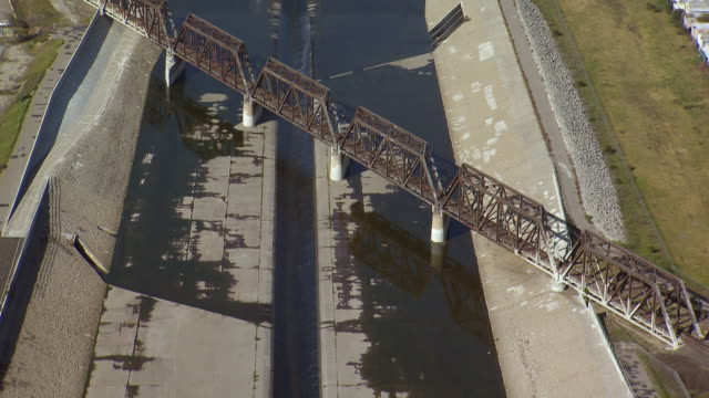 aerial view of a metal railroad bridge crossing the cement embankments of the los angeles river. - zement stock-videos und b-roll-filmmaterial