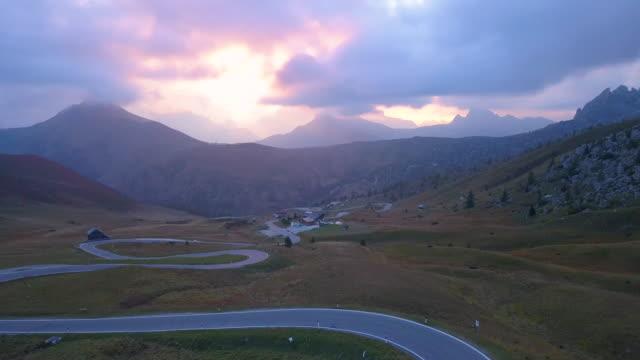 stockvideo's en b-roll-footage met luchtfoto van een bergweg in dolomieten alpen bij zonsondergang - verwonderingsdrang