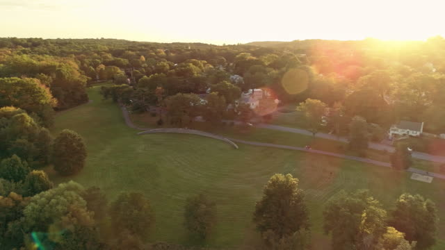 aerial view of a park and residential area in springfield, new jersey, usa, at sunset. drone video with the panoramic camera motion. - small town stock videos & royalty-free footage