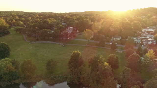 aerial view of a park and residential area in springfield, new jersey, usa, at sunset. drone video with the panoramic camera motion. - new jersey stock videos & royalty-free footage