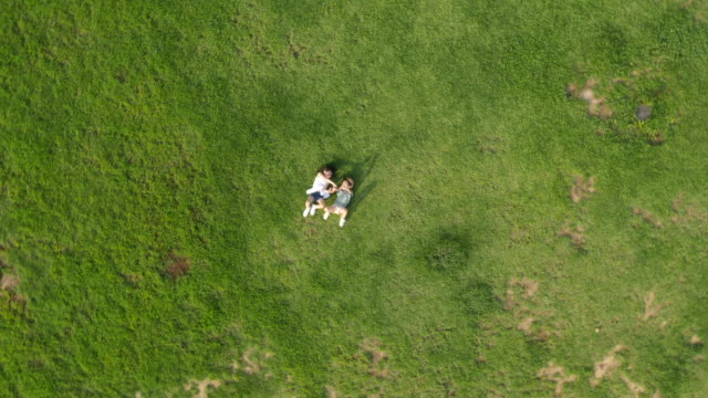 aerial view of a playful boy and a girl lying on lawn toward the sky in summer at seoulforest (the third largest park in seoul city) - lawn stock videos & royalty-free footage