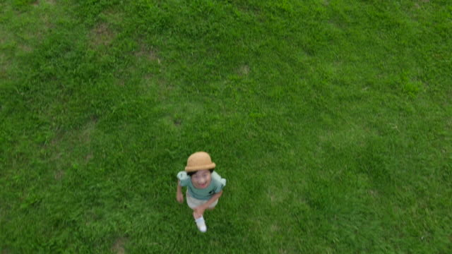 Aerial view of a playful boy playing with a camera in summer at Seoulforest (the third largest park in Seoul city)