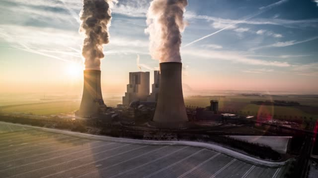 aerial view of a power station in back light - smoke stack stock videos & royalty-free footage