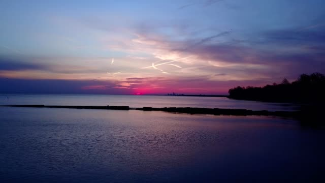 aerial view of a purple sunset over a lake in cleveland ohio - lago erie video stock e b–roll