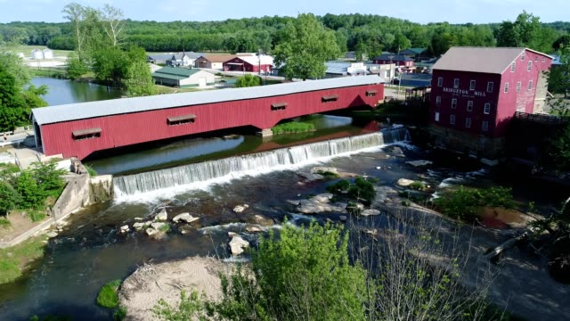 aerial view of a red wooden covered bridge in bridgeton indiana - amische stock-videos und b-roll-filmmaterial