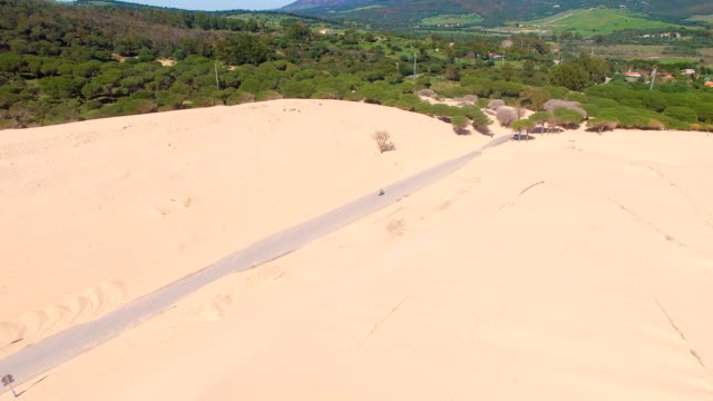 stockvideo's en b-roll-footage met aerial view of a road buried by dune sand in the desert - silvestre