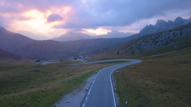 aerial view of a road in dolomites mountains at sunset - mountain road stock videos & royalty-free footage