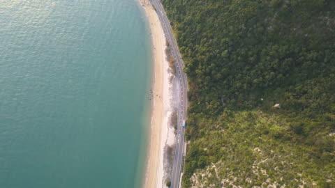 vídeos y material grabado en eventos de stock de vista aérea de una carretera entre una montaña y el océano - coastline
