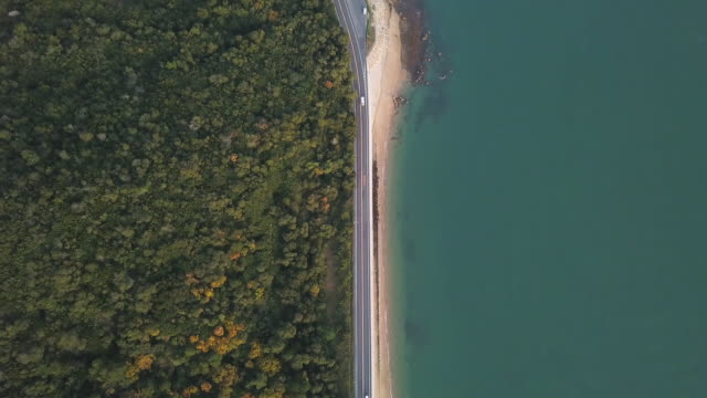 vídeos de stock e filmes b-roll de aerial view of a road running between a mountain and the ocean - dispersa