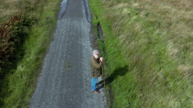 スコットランドの田舎道を歩く高齢者の航空写真 - 羊飼いの棒点の映像素材/bロール