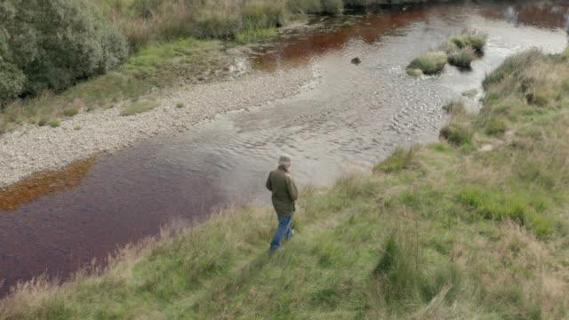 luftaufnahme eines älteren mannes, der neben einem kleinen schottischen fluss spazieren geht - full length stock-videos und b-roll-filmmaterial