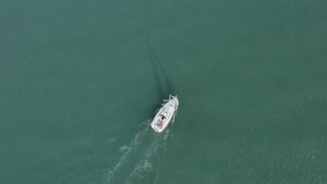 vidéos et rushes de aerial view of a single sailboat on calm green waters off the south coast of england, uk. - bercement
