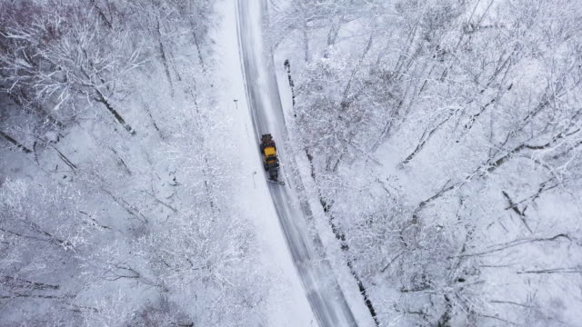 aerial view of a snowplow driving through snow - snowplough stock videos & royalty-free footage