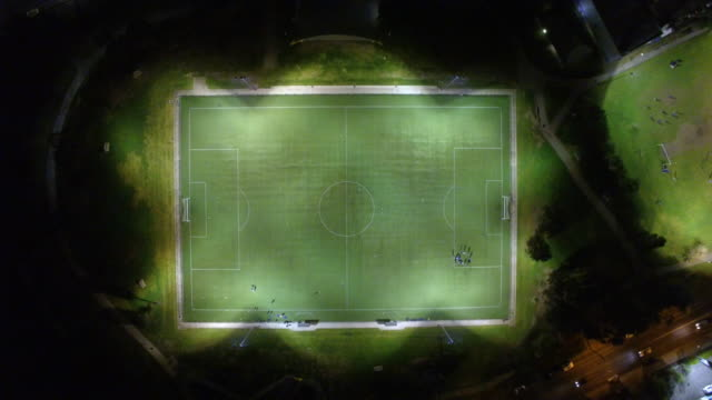 aerial view of a soccer sports ground at night. - football pitch stock videos and b-roll footage