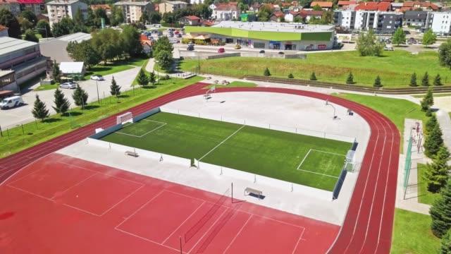 ランニングトラック、サッカー、バスケットボールを備えたスポーツアスレチックとレクリエーションセンターの空中写真 - 球技場点の映像素材/bロール