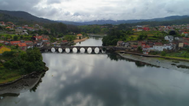 aerial view of a stone bridge with cars driving across a river in pontevedra, spain - galicia stock videos & royalty-free footage