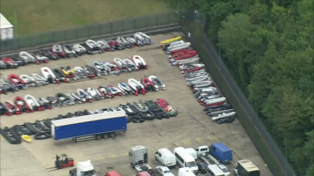 aerial view of a storage yard in dover full of seized migrant boats used to cross the english channel - trapped stock videos & royalty-free footage